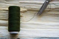 Fil et ciseaux de couture sur la planche en bois Photo libre de droits