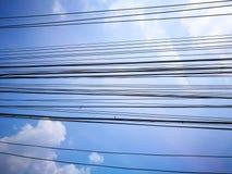 Fil noir de câble électrique montrant sur un fond de ciel bleu Photos stock