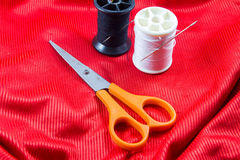 Fil noir et blanc de couleur avec des ciseaux oranges Photo stock