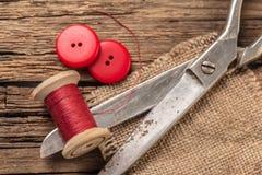 Fil rouge avec des boutons et des ciseaux Photographie stock libre de droits