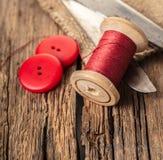 Fil rouge avec des boutons et des ciseaux Image stock