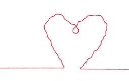Fil rouge dans la forme de signe de coeur Photographie stock