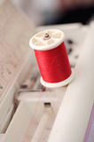 Fil rouge dans la profondeur de machines à coudre du champ (foyer mou Images stock