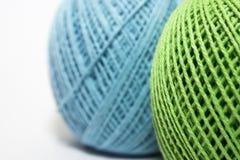 Fil vert et bleu pour tricoter sur le fond blanc Photographie stock