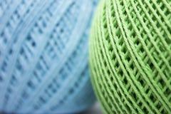 Fil vert et bleu pour tricoter sur le fond blanc Photo libre de droits