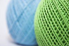 Fil vert et bleu pour tricoter sur le fond blanc Image libre de droits