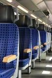 Fila de asientos azules vacíos en un tren Fotos de archivo