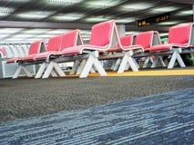 Fila de asientos en área de la salida en terminal de aeropuerto Foto de archivo