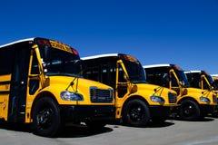 Fila de autobuses escolares a estrenar en una representación fotos de archivo libres de regalías