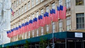 Fila de banderas americanas en Saks Fifth Avenue, New York City imagenes de archivo