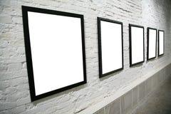 Fila de bastidores negros en la pared de ladrillo blanca Imagen de archivo