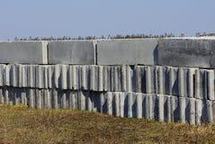 Fila de bloques de cemento grises en exterior de la hierba seca foto de archivo