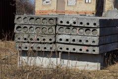 Fila de bloques de cemento grises viejos en hierba seca en un emplazamiento de la obra imagen de archivo