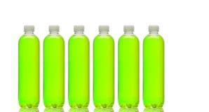 Fila de botellas con la bebida verde Fotos de archivo