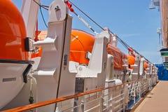 Fila de botes salvavidas anaranjados de Deck del barco de cruceros Imagenes de archivo