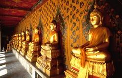 Fila de Buddhas de oro en templo tailandés Imágenes de archivo libres de regalías