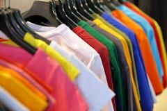 Fila de camisetas en guardarropa o tienda Imagen de archivo libre de regalías
