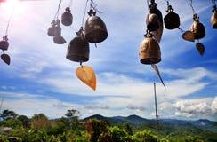 Fila de campanas de oro en templo budista Fondo de montañas en Asia, tailandia Imagen de archivo libre de regalías