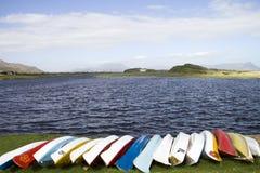 Fila de canoas en una orilla del lago Foto de archivo libre de regalías