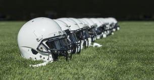Fila de cascos de fútbol americano americanos antes de un juego Imagen de archivo libre de regalías