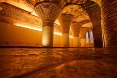 Fila de columnas arqueadas antiguas iluminadas de oro Fotos de archivo