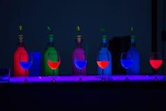 Fila de copas con los líquidos multicolores en la luz ultravioleta imagenes de archivo