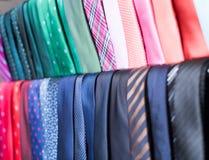 Fila de corbatas en suspensiones en tienda de ropa de los hombres Foto de archivo libre de regalías