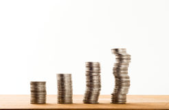 Fila de cuatro monedas en la tabla de madera foto de archivo libre de regalías