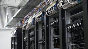 Fila de la disposición de los mineros del bitcoin en los shelfs atados con alambre Ordenador para la explotación minera de Bitcoi almacen de video