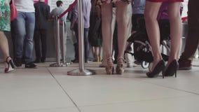 Fila de la gente que espera en un aeropuerto Pies de gente en línea en el aeropuerto almacen de video