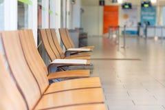 Fila de la silla de madera en sala de espera en el aeropuerto Imagen de archivo libre de regalías