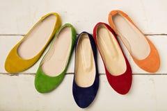 Fila de las bailarinas coloridas de los zapatos en un fondo de madera blanco Imagenes de archivo