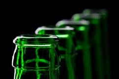 Fila de las botellas de cerveza verdes abiertas Imagen de archivo libre de regalías