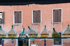 Fila de las botellas de cristal medias llenas con agua que muestra la reflexión del canal del agua de Venecia Imagen de archivo