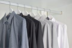 Fila de las camisas blancas, grises, negras que cuelgan en guardarropa de madera Fotografía de archivo