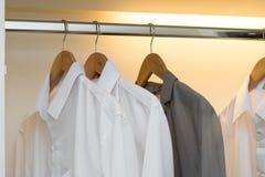 Fila de las camisas blancas y grises en el guardarropa blanco Fotografía de archivo