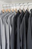 Fila de las camisas negras y grises que cuelgan en la suspensión de capa Imagenes de archivo