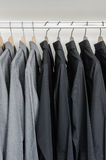 Fila de las camisas negras y grises que cuelgan en la suspensión de capa Fotografía de archivo