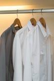 Fila de las camisas que cuelgan en el guardarropa blanco Fotos de archivo libres de regalías