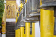 Fila de las campanas de bronce fuera de un templo budista de oro Fotografía de archivo