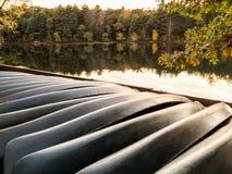 Fila de las canoas de alquiler volcadas a lo largo de orilla del lago foto de archivo