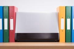 Fila de las carpetas de la oficina y del ordenador portátil coloreados del ordenador Fotos de archivo libres de regalías