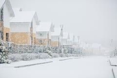 Fila de las casas sitiadas por la nieve, hogares con la acera en el st vacío Imagen de archivo