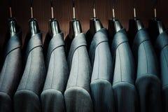 Fila de las chaquetas del traje de los hombres en suspensiones Imagen de archivo