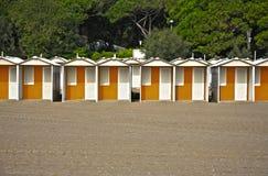Fila de las chozas coloridas de la playa en una playa arenosa Foto de archivo libre de regalías