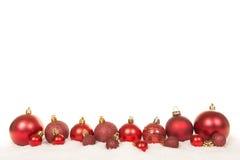 Fila de las decoraciones rojas de la bola de la Navidad y del ilex verde del acebo en la nieve Fotos de archivo libres de regalías