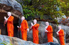 Fila de las estatuas del monje budista en trajes monásticos anaranjados imagen de archivo libre de regalías