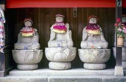 Fila de las estatuas del monje de Jizo con el babero y el sombrero - Japón fotografía de archivo