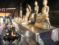 Fila de las estatuas de oro de Buda en banco con las llamas que queman abajo Fotos de archivo