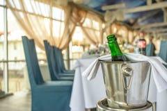 Fila de las flautas de champán y de dos botellas en los cubos de hielo listos para la tostada de colada Imagenes de archivo